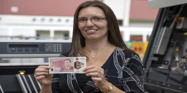 In this photo provided by the Bank of England on Thursday, March 25, 2021,S arah John, Chief Cashier at the Bank of England, holds the new 50-pound note featuring scientist Alan Turing. The rainbow flag is flying proudly above the Bank of England in the heart of London's financial district to commemorate legendary World War II codebreaker Alan Turing, the new face of Britain's 50-pound note. The design of the banknote, which is the most valuable in circulation, was unveiled Thursday before it is formally issued on June 23, Turing's birthday. (Bank of England via AP)