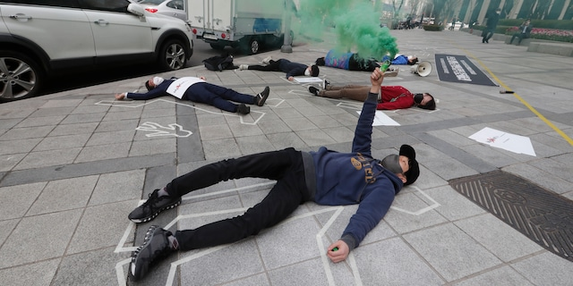 South Korean peace activists lie on a street to pay tribute to the victims of the recent protests in Burma, during a rally against Burma's military coup in Seoul, South Korea, Friday, March 26, 2021. (AP Photo/Ahn Young-joon)