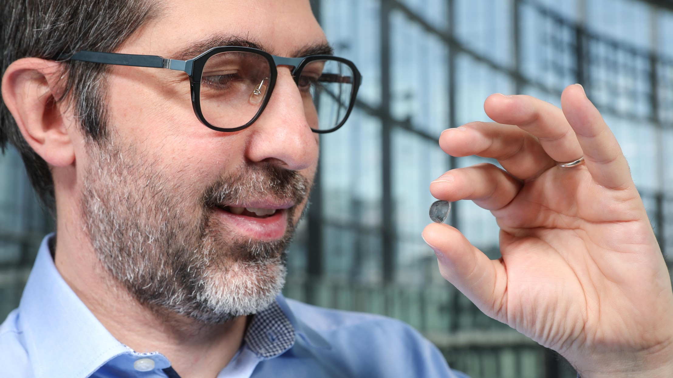 Researcher Diego Ghezzi holds a contact lens with photovoltaic dots on it.