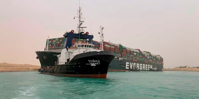 In this photo released by the Suez Canal Authority, a boat navigates in front of a massive cargo ship, named the MV Ever Given, rear, sits grounded Wednesday, March 24, 2021. (Suez Canal Authority via AP)