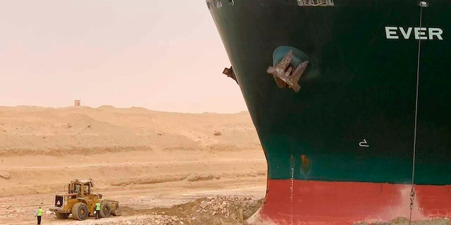 In this photo released by the Suez Canal Authority, a cargo ship, named the MV Ever Given, sits with its bow stuck into the wall Wednesday, March 24, 2021. (Suez Canal Authority via AP)