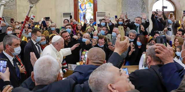 Pope Francis arrives at a meeting with the Qaraqosh community at the Church of the Immaculate Conception, in Qaraqosh, Iraq, Sunday, March 7, 2021. A small Christian community returned to Qaraqosh after the war where they rebuilt their church that had been used as a firing range by IS. (AP Photo/Andrew Medichini)
