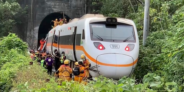 Rescue workers gather near one end of the train involved in a derailment. (AP/Executive Yuan)