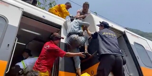 A passenger, center, is helped to climb out of the derailed train. (AP/hsnews.com.tw)