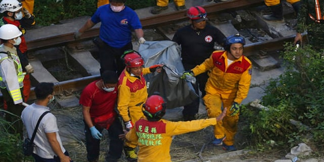 Rescue workers recover a body from a derailed train near the Taroko Gorge area in Hualien, Taiwan, on Friday. (AP)