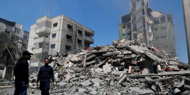 Hamas police officer stands guard amid the rubble of the Yazegi residential building that was destroyed by an Israeli airstrike, in Gaza City, Sunday, May 16, 2021. (AP Photo/Adel Hana)
