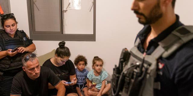 A family huddles in their home with bomb technicians and police as sirens warn of an incoming attack, Thursday, May 20, 2021, in Ashkelon, southern Israel. The family residence had just received a direct hit from an unexploded missile that landed on the top floor of their high rise apartment building.