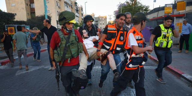 Israeli security forces and paramedics carry a wounded Jewish man after he was shot during violent unrest in Lod, Israel, Thursday, May 13, 2021.