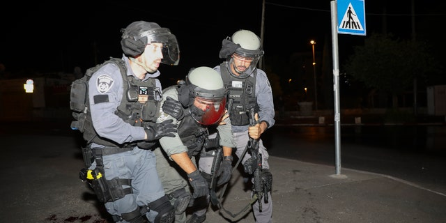 An injured Israeli police officer is helped during clashes with Palestinian protesters, in east Jerusalem, Friday, May 7, 2021. Palestinians protested following Israel's threatened eviction of dozens of Palestinians in the Sheikh Jarrah neighborhood in east Jerusalem, who have been embroiled in a long legal battle with Israeli settlers trying to acquire property in the neighborhood. (AP Photo/Mahmoud Illean)
