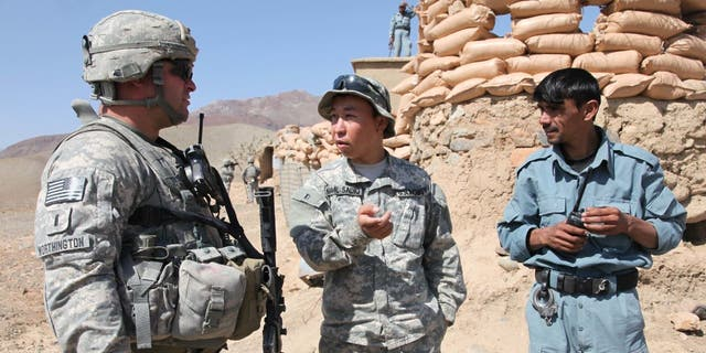 U.S. Army 1st Lt. Paul Worthington (left) listens to an interpreter while speaking with an Afghan National Policeman about security issues during a visit to a National Police outpost in the Jabal Saraj district of the Parwan province of Afghanistan on Oct. 8, 2010.