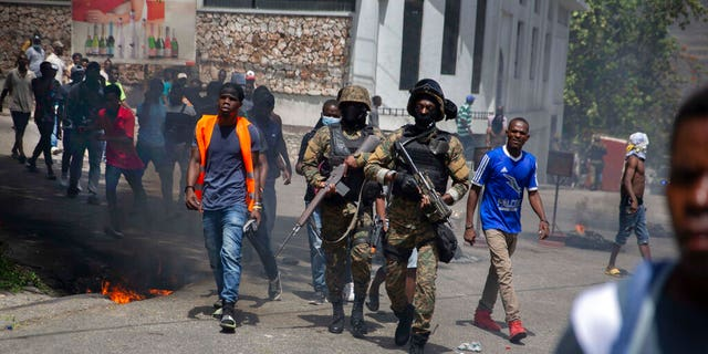 Police walk among protesters during a protest against the assassination of Haitian President Jovenel Moïse near the police station of Petion Ville in Port-au-Prince, Haiti, Thursday, July 8, 2021.