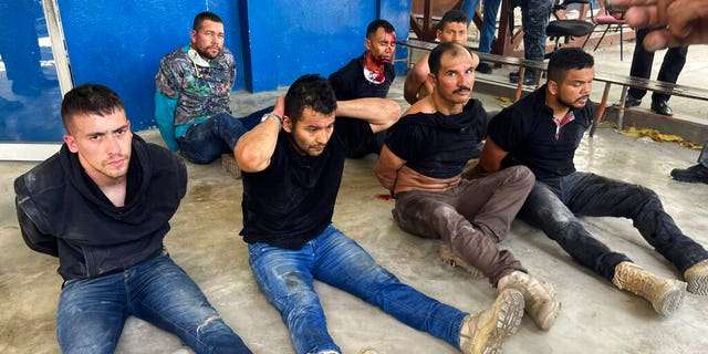 Suspects in the assassination of Haiti's President Jovenel Moise sit on the floor handcuffed after being detained, at the General Direction of the police in Port-au-Prince, Haiti, Thursday, July 8, 2021.