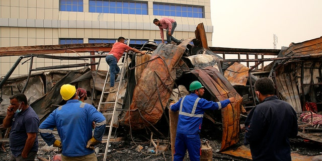 Rescuers and civilians look for bodies after a catastrophic blaze erupted Monday at a coronavirus hospital ward in the al-Hussein Teaching Hospital, in Nasiriyah, Iraq, Tuesday, July 13, 2021.