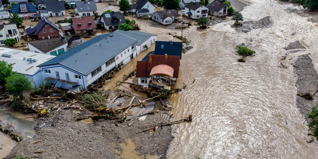 Damaged houses are seen at the Ahr river in Insul, western Germany, Thursday, July 15, 2021. Due to heavy rain falls the Ahr river dramatically went over the banks the evening before. People have died and dozens of people are missing in Germany after heavy flooding turned streams and streets into raging torrents, sweeping away cars and causing some buildings to collapse. (AP Photo/Michael Probst)