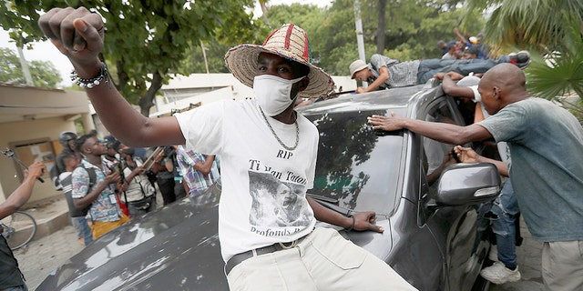 Supporters of former Senator Steven Benoit shout outside the courthouse as he departs after being called in for questioning, in Port-au-Prince, Monday, July 12, 2021. Prosecutors have requested that high-profile politicians like Benoit meet officials for questioning as part of the investigation into the assassination of President Jovenel Moise. (AP Photo/Fernando Llano)