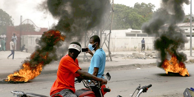 Supporters of former Senator Youri Latortue and Steven Benoit set tires on fire outside the court house in Port-au-Prince, Monday, July 12, 2021. Prosecutors have requested that high-profile politicians like Latortue and Benoit meet officials for questioning as part of the investigation into the assassination of President Jovenel Moise. (AP Photo/Joseph Odelyn)