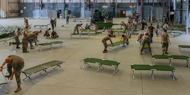 U.S. military personnel and volunteers prepare cots for arriving evacuees at Ramstein Air Base in Germany. (Ramstein Air Base)