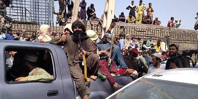Taliban fighters sit on a vehicle along the street in Jalalabad on August 15, 2021. (Getty Images)