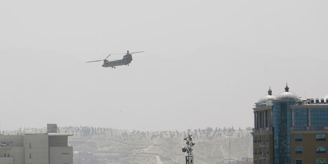 A U.S. Chinook helicopter flies near the U.S. Embassy, left, in Kabul, Afghanistan, Sunday, Aug. 15, 2021. (Associated Press)