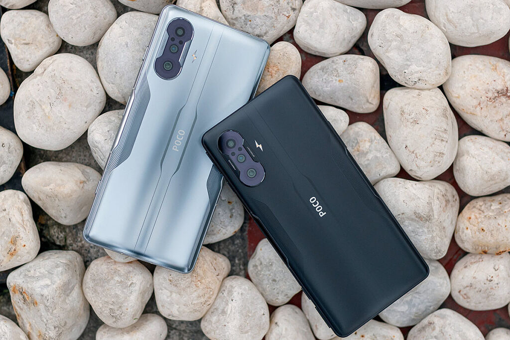 Silver and black POCO F3 GT on pebbles