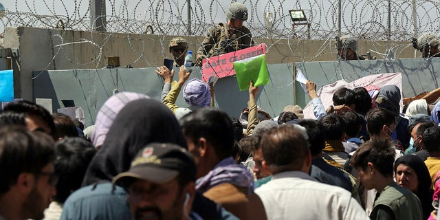 A U.S. soldier holds a sign indicating a gate is closed as hundreds of people gather near an evacuation control checkpoint on the perimeter of the Hamid Karzai International Airport, in Kabul, Afghanistan on Aug. 26, 2021. (AP Photo/Wali Sabawoon, File)