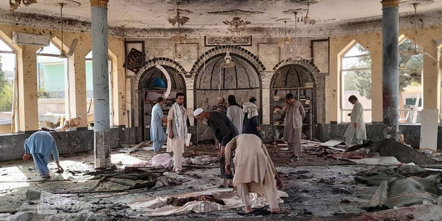 People view the damage inside of a mosque following a bombing in Kunduz, province northern Afghanistan, Friday, Oct. 8, 2021. (AP Photo/Abdullah Sahil)