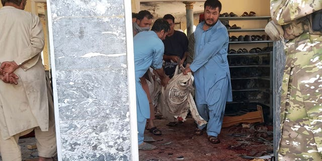 People carry the body of a victim following a bombing in Kunduz province, northern Afghanistan, Friday, Oct. 8, 2021. A powerful explosion in a mosque frequented by a Muslim religious minority in northern Afghanistan on Friday has left several casualties, witnesses and the Taliban's spokesman said. (AP Photo/Abdullah Sahil)